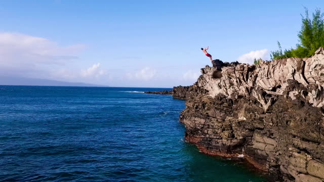Aerial View Cliff Jumping into Blue Ocean. Summer Action Sports Lifestyle. Young Man Jumps off Cliff in Slow Motion. Cliff Jumping into Ocean. Aerial View Slow Motion. Young Man Jumps off Cliff Into Blue Ocean. Summer Extreme Sports Outdoor Lifestyle. cliff jumping stock videos & royalty-free footage