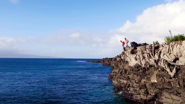 Aerial View Cliff Jumping into Blue Ocean. Young Man Jumps off Cliff in Slow Motion. Summer Extreme Sports. Cliff Jumping into Ocean. Aerial View Slow Motion. Young Man Jumps off Cliff Into Blue Ocean. Summer Extreme Sports Outdoor Lifestyle. cliff jumping stock videos & royalty-free footage
