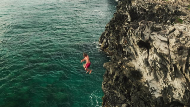 Aerial view cliff jumping into ocean video