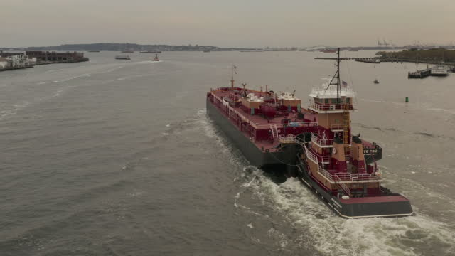 ニューヨーク市の港で水に割り込みを押す赤いタグボートで後ろから近づいてくる空中写真 - はしけ点の映像素材/bロール