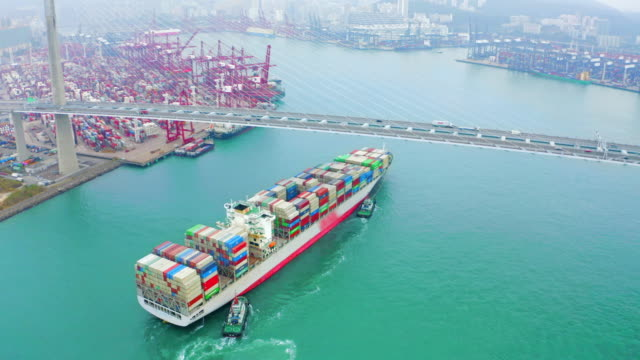 aerial view container cargo ship going to terminal commercial port or container warehouse with hong kong cityscape for business logistics, import export, shipping or transportation. - nave mercantile video stock e b–roll