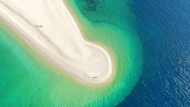 aerial view couple flying drone off sunny,tranquil beach on bol - zlatni rat,island of brac,croatia - wyspa land feature filmów i materiałów b-roll