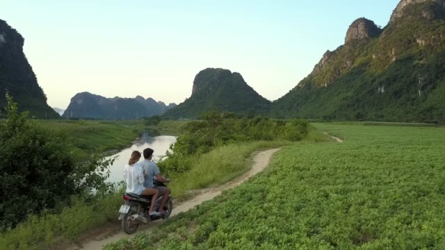 Video aerial view couple travels on scooter along green fields