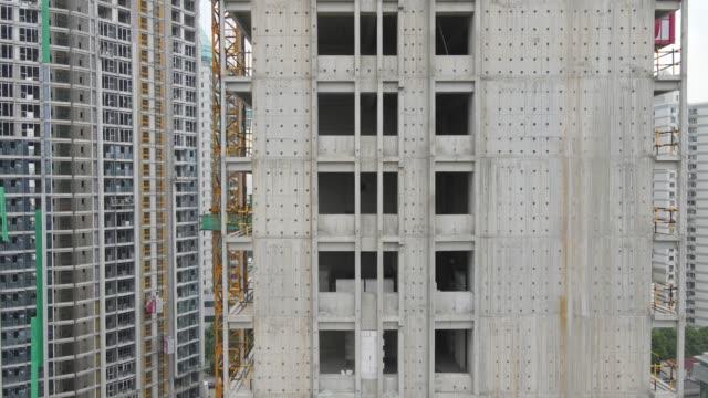 vídeos y material grabado en eventos de stock de vista aérea drone volar alrededor de rascacielos en el sitio de construcción lugar de trabajo épico - imperfección