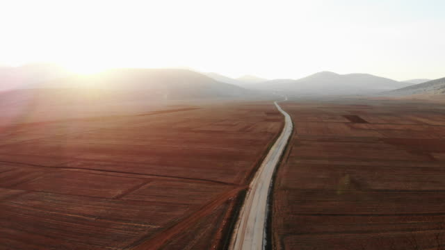Aerial view Drone Footage of road with red field with background of mountain