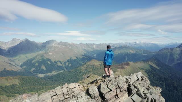航空写真。山の上の若者の周りを移動するドローン - 崖点の映像素材/bロール