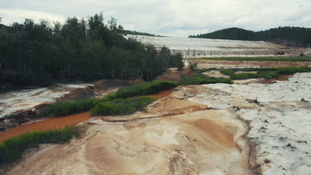 Aerial view; drone moving forward over polluted river Aerial view; drone flying forward over a polluted river with destroyed ecosystem and copper tailing dump poisoning ground and water; air emissions from industry; environmental disaster in South Ural dry stock videos & royalty-free footage