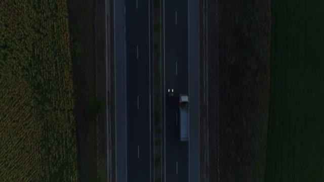 vídeos de stock, filmes e b-roll de vista aérea drone voador revelando ao longo da estrada após o pôr do sol - estrada principal estrada