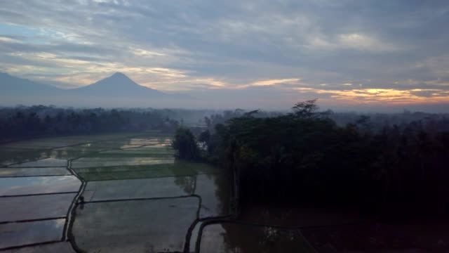 Aerial view drone shot of Borobudur town in Java at sunrise, Indonesia Travel religion drone concept 4K resolution Rice fields and volcano