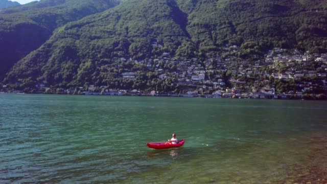 vídeos de stock e filmes b-roll de aerial view drone shot of young man paddling on beautiful mountain lake in summer enjoying nature and environment. male canoeing on swiss lake - lago maggiore