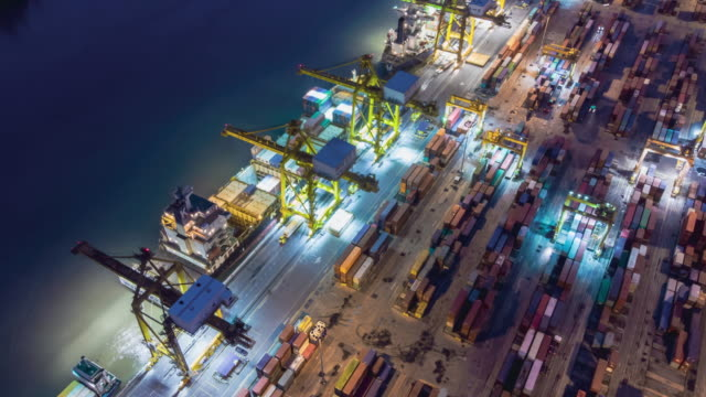 vídeos de stock e filmes b-roll de aerial view drone time-lapse or hyper-lapse over industrial port in bangkok thailand with many container vessel ship and big crane working at night. - drone shipyard night