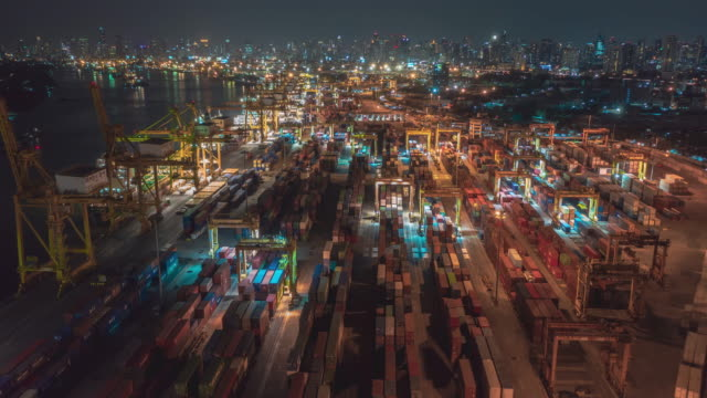Video Aerial view drone time-lapse or hyper-lapse over industrial port in Bangkok Thailand with many container vessel ship and big crane working at night.