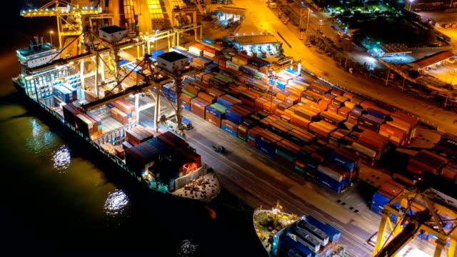 havadan görünümü dron-sukut veya hızlandırılmış endüstriyel bağlantı noktası veya tersane ile konteyner gemi güney doğu asya'da geceleri - dalgakıran stok videoları ve detay görüntü çekimi