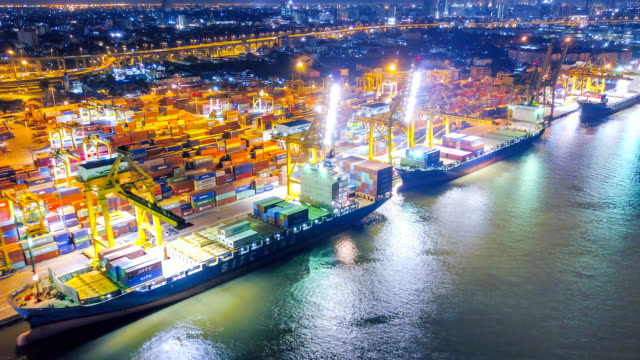 vídeos de stock e filmes b-roll de aerial view drone-lapse or time-lapse of industrial port with containers ship at night in south east asia - docas