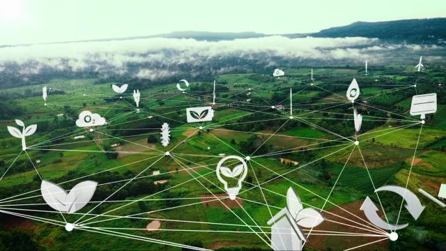 空中写真、山の近くのグリーンファームフィールド上のネットワークとエコロジーアイコン - 鎖の輪点の映像素材/bロール