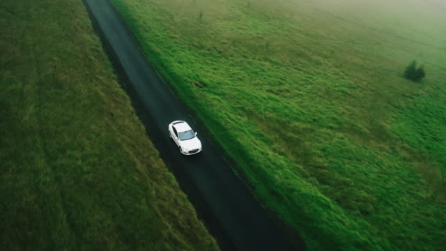 Aerial view electric car driving on country road Aerial view electric car driving on country road, luxury car driving through mist at dusk with headlights sports car stock videos & royalty-free footage