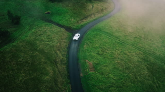Aerial view electric car driving on country road Aerial view electric car driving on country road, luxury car driving through mist at dusk with headlights luxury car stock videos & royalty-free footage