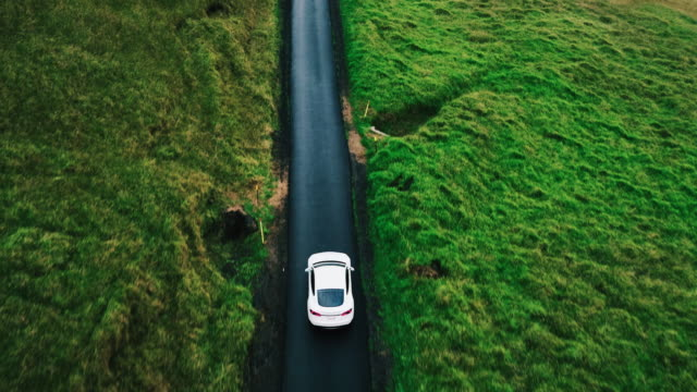 Aerial view electric car driving on country road Aerial view electric car driving on country road, luxury car driving through mist at dusk with headlights alternative fuel vehicle videos stock videos & royalty-free footage