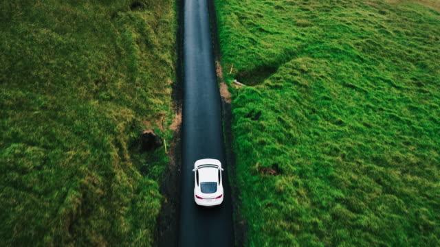 havadan görünümü elektrikli otomobil sürüş ülke yolda - araba kullanımı stok videoları ve detay görüntü çekimi