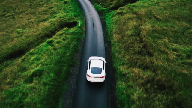 aerial view electric car driving on country road - aerial road stock videos & royalty-free footage