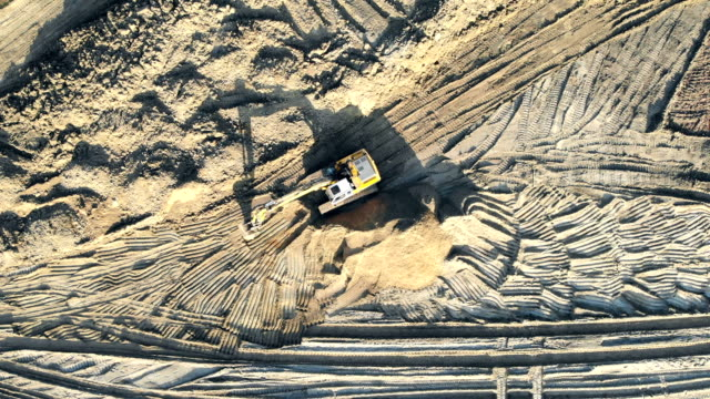Aerial view excavator clears the construction site. A look at the construction from a height Aerial view excavator clears the construction site. A look at the construction from a height. construction vehicle stock videos & royalty-free footage