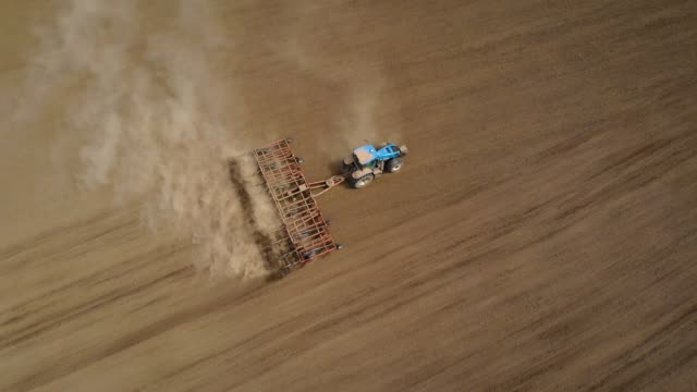 Aerial view farm tractor with disk plow and harrows preparing field for sowing crops Aerial view farm tractor with disk plow and harrows preparing field for sowing crops. Spring agronomic activity on agricultural land harrow agricultural equipment stock videos & royalty-free footage