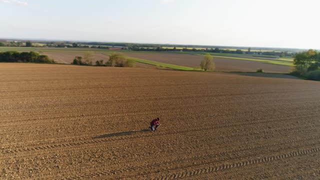 ws-antenne ansicht landwirt prüfung schmutz im sonnigen, großen, ländlichen gepflügtes feld - aerial overview soil stock-videos und b-roll-filmmaterial