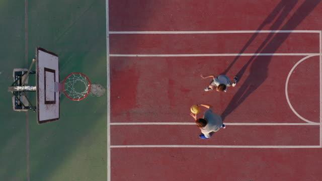 Luchtfoto. vader en zoon spelen basketbal op de baan buitenshuis video
