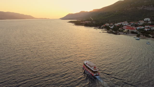 WS Aerial view ferry boat moving along tranquil ocean at sunset,Peljesac,Croatia