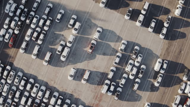 aerial view flying above car storage parking lot for new and unsold cars - ultra high definition television filmów i materiałów b-roll