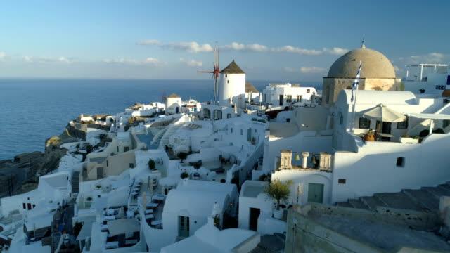 aerial view flying over city of oia on santorini greece - morze egejskie filmów i materiałów b-roll