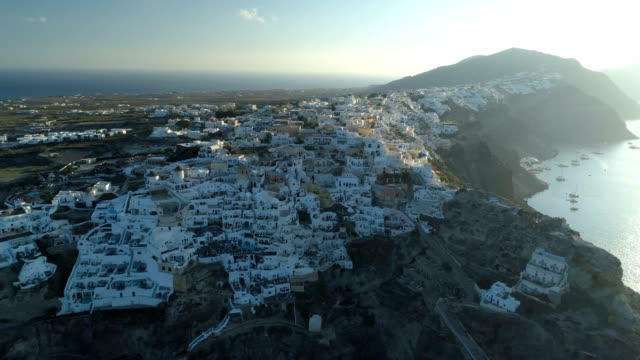 Aerial view flying over city of Oia on Santorini Greece Aerial view flying over city of Oia on Santorini Greece, early morning aegean sea stock videos & royalty-free footage