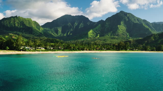Aerial view flying over hawaiian canoes towards beautiful green mountains and video