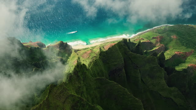 Aerial view flying over jungle mountain peaks, Na Pali coast Kauai Aerial view flying over jungle mountain peaks revealing tropical coastline, Na Pali coast Kauai hawaii islands stock videos & royalty-free footage