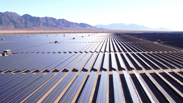 Aerial view flying over large industrial solar energy farm in desert video