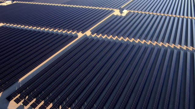 Aerial view flying over large solar farm in desert creating clean renewable energy video