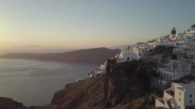 Aerial view flying over Santorini, Greece, greek island with white houses and blue roofs in summer. Santorini from drone. Aerial footage of greek island in summer. Oia, Thira, Imerovigli, Aegean sea. Sunset on Oia (Santorini). Sunrise on Sunshine. Blue sky. greek islands stock videos & royalty-free footage