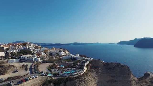 aerial view flying over santorini, greece, greek island with white houses and blue roofs in summer. - fire filmów i materiałów b-roll