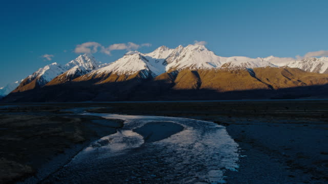 Aerial view flying over snow melt rivers towards snowy mountain peaks in New Zealand video