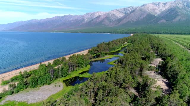 vídeos de stock e filmes b-roll de aerial view. flying over the beautiful lake near mountains. a. - lago baikal