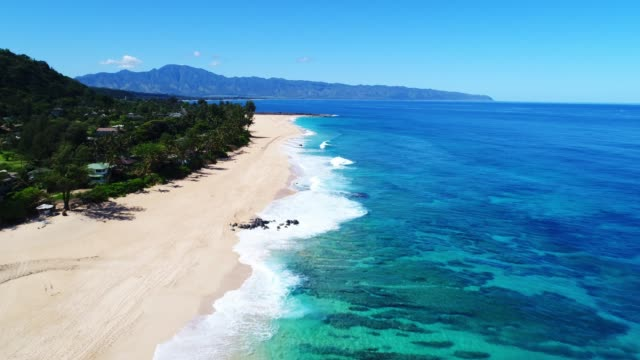 Aerial view flying over tropical white sand beach and clear blue water ocean on the North Shore of Hawaii on sunny day