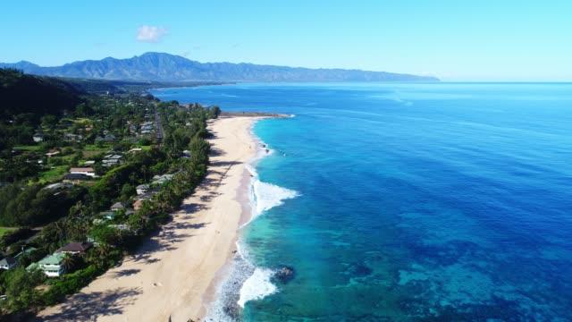 熱帯の白上を飛んで空撮は白砂の浜と晴れた日にハワイの北海岸で青い水の海をクリア - ハワイ点の映像素材/bロール