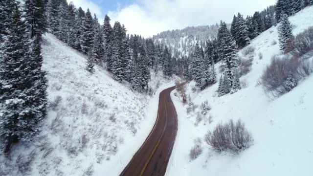 Aerial view flying through windy snow covered canyon road video