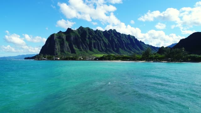Aerial view flying towards lush jungle mountain landscape on the east side of Oahu in Hawaii Aerial drone shot filmed on the east side of Oahu mountain range where the ocean water meets the mountains oahu stock videos & royalty-free footage