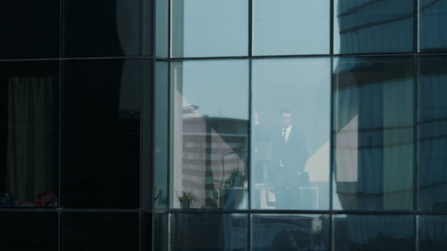vídeos de stock, filmes e b-roll de imagens aéreas de exibição: de fora em prédio de escritórios com empresário trabalhando e olhando pela janela. é lindo voar zoom shot de arranha-céus do distrito financeiro de negócios. - promoção emprego