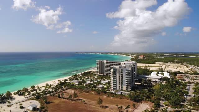stockvideo's en b-roll-footage met luchtfotobeelden van kustlijn van grand cayman, kaaimaneilanden stockvideo kaaimaneilanden, grand cayman, caraïben, tourist resort, hotel - blue sky
