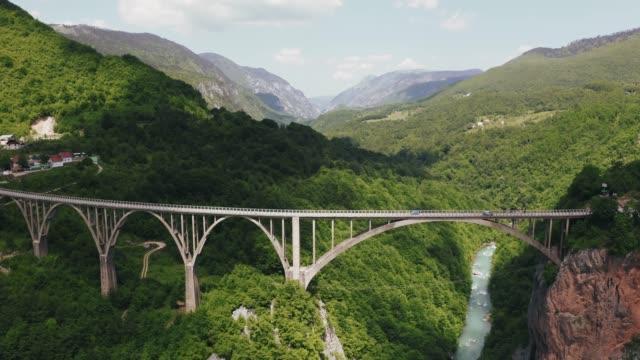 riprese aeree del ponte ad arco durdevica tara sulle montagne del montenegro - canyon video stock e b–roll