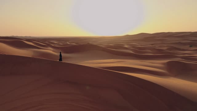 Aerial view from a drone flying next to a woman in abaya United Arab Emirates
