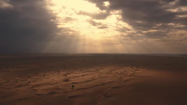 vídeos de stock, filmes e b-roll de vista aérea de um drone voando ao lado de uma mulher em abaya (vestido tradicional dos emirados árabes unidos) andando sobre as dunas no deserto - deserto