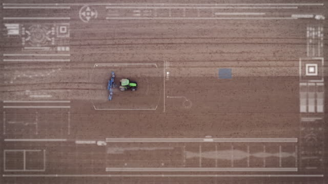 Aerial view from a futuristic machine while scanning a tractor working in the In fields.